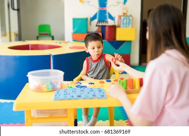 Toddler learning the alphabet with a language therapist in a special education class