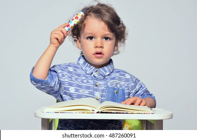 Toddler learning how to write and read. Small kid having fun preparing for school and drawing on a book and pretending to think