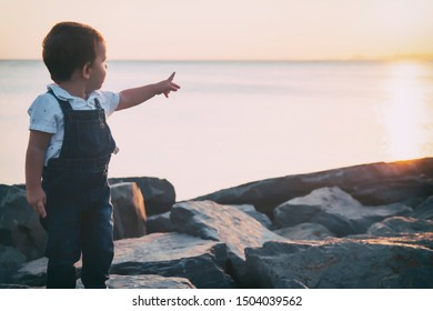 Toddler looking and pointing with his hand to sky during sunset