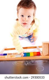 Toddler near blackboard, shot from top