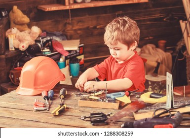 Toddler on busy face plays with tools at home in workshop. Kid boy play as handyman. Child cute and adorable playing with tools as builder or repairer, repairing or handcrafting. Childhood concept.