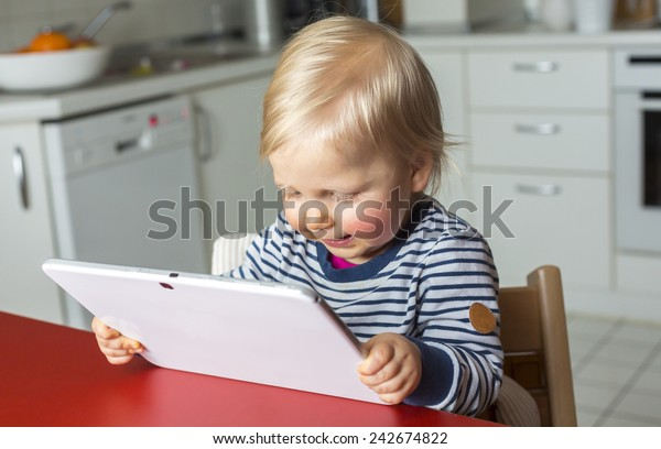 Toddler on a highchair reading a tablet pc