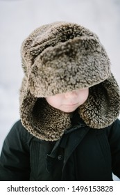 toddler in oversized fur trapper hat in the snow