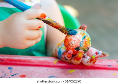 Toddler painting a polystyrene ball