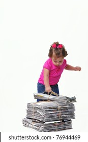 Toddler placing a stack of paper ready for recycling, teaching them to care about the environment when they are at an early age.
