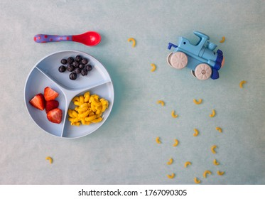 Toddler plate with macaroni and cheese, strawberries and blueberries with toy train and spread pasta around the food