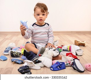 Toddler playing with a lot of baby shoes holding one shoe up. Untidy stack of child shoes thrown on the ground.