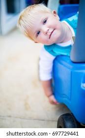 Toddler playing in blue car