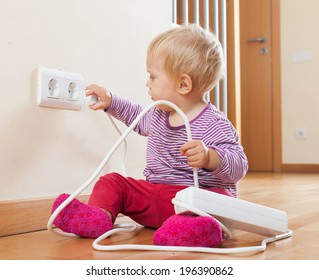 Toddler playing with extension cord at home