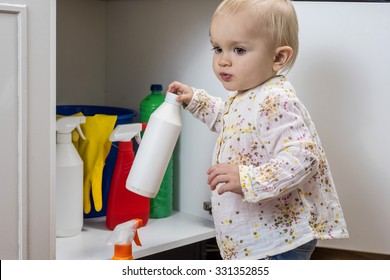 Toddler playing with household cleaners at home
