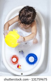 Toddler playing with soap foam / A colored bath-time for kids