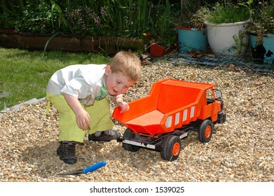Toddler playing with toy in garden.  Youth concept.