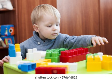 toddler  reaching for a toy constructor indoor