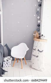 Toddler room with white cradle, chair and storage bag