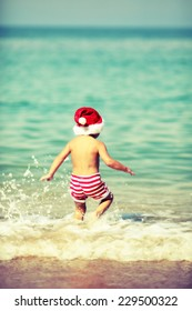 toddler Santa Claus on beach