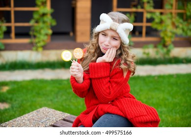 Toddler school girl sitting on bench with candies, holding her cheek because of teeth pain and cry