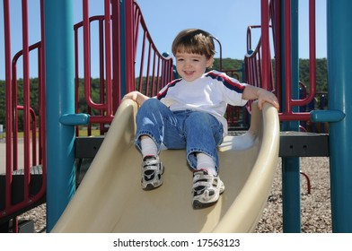 A toddler shows his excitement as he is about to take off on a slide in a neighborhood playground