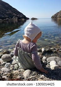 Toddler sitting by the sea, calm lovely weather in the South of Norway. Picture tanken in April. Nice little hike to get to this place, peaceful and mindfull.