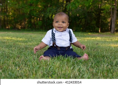 A toddler sitting in the grass