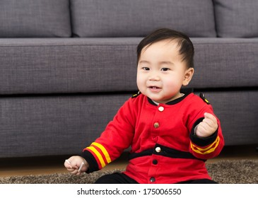 Toddler sitting on carpet at home
