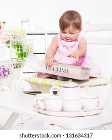 Toddler sitting on chair and playing with the tea set