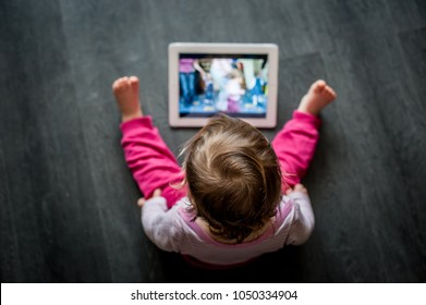 toddler sitting on the floor looking at tablet screen