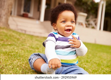 Toddler sitting on the grass in a garden