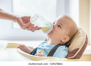 toddler sitting at the table and drinking milk