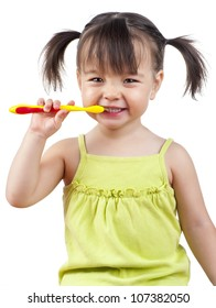 Toddler smiling while brushing her teeth isolated on white