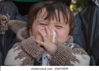 toddler sneezing with napkin