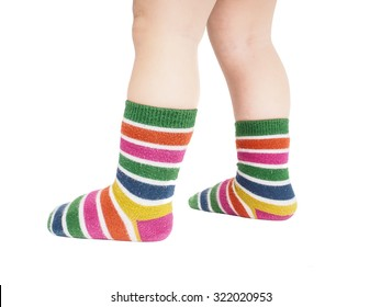 Toddler standing in striped socks and bare legs isolated on white
