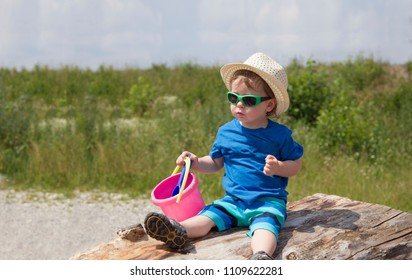 A toddler with straw hat wearing sunglasses and sand toy in hand sits on a tree trunk