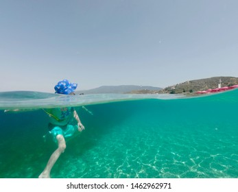 Toddler swimming in crystal clear blue waters with a floatation device as help. All necessary precautions are taken for sun burn protection such as hat, shirt and sunscreen.