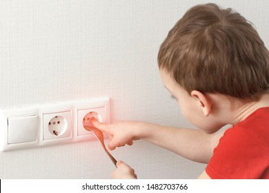 Toddler touches a power outlet. Dangerous children games at home with electricity. - Shutterstock ID 1482703766