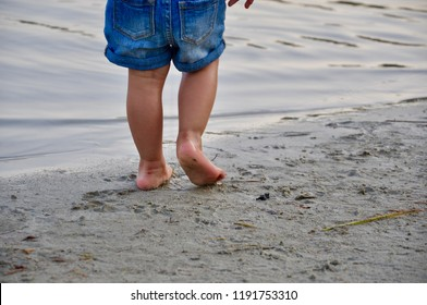Toddler walking barefoot in the sand