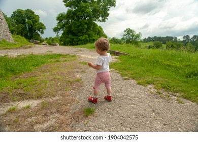 The toddler is walking outdoor.