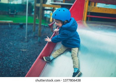 A toddler wearing a helmet is coming down a slide in the playground