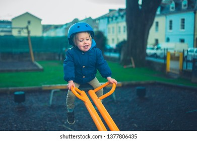 A toddler wearing a helmet is sitting on the seesaw in the playground