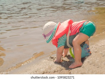 Toddler wears life jacket at the beach