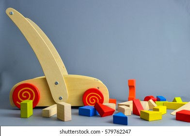 Toddler wooden walker wagon with cubes and other geometrical shapes spread on the ground, painted in various lively colors on grey background. Copy space or room for text.