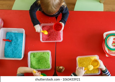 Toddlers playing with sensory box with colourful rice on red table. Top view.