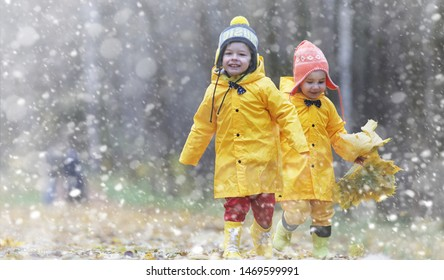 Toddlers walk in the autumn park. First frost and the first snow in the autumn forest. Children play in the park with snow and leaves.