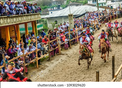 Todos Santos Cuchumatan, Guatemala - November 1, 2011: Traditionally dressed indigenous locals & tourists watch drunken men from town race up & down dirt track on horseback all day on All Saints's Day