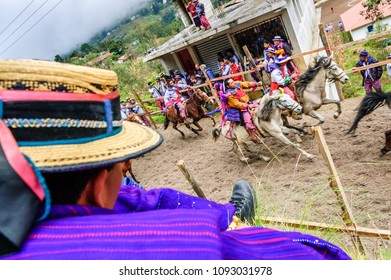 Todos Santos Cuchumatan, Guatemala - November 1, 2011: Traditionally dressed indigenous Mam locals & tourists watch drunken men from town race up & down dirt track on horseback on All Saints' Day.