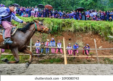Todos Santos Cuchumatan, Guatemala - November 1, 2011: Traditionally dressed indigenous Mam locals & tourists watch drunken men race up & down dirt track on horseback all day on All Saints' Day.