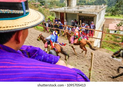 Todos Santos Cuchumatan, Guatemala - November 1, 2011: Traditionally dressed indigenous locals & tourists watch drunken men from town race up & down dirt track on horseback on All Saints' Day.