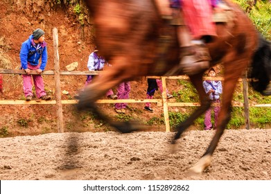Todos Santos Cuchumatan, Guatemala - November 1, 2011: Traditionally dressed indigenous Mam locals watch inebriated men race horseback along dirt track all day on All Saints' Day.