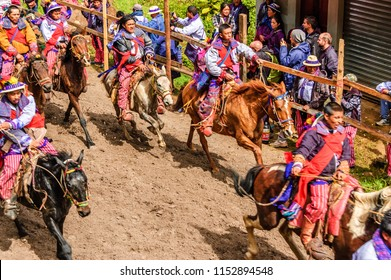 Todos Santos Cuchumatan, Guatemala - November 1, 2011: Traditionally dressed inebriated indigenous Mam men race horseback along dirt track all day on All Saints' Day watched by locals & tourists..