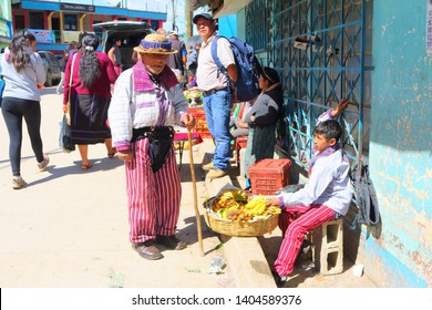 TODOS SANTOS CUCHUMATAN; GUATEMALA - NOVEMBER 2018: an unidentified local child sells his bananas to an old men on the market on November 17, 2018 in Todos Santos Cuchumatan.