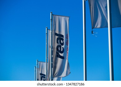 TOENISVORST, GERMANY - MARCH 22. 2019: Flags with logo of Real (German supermarket chain) against clear blue sky